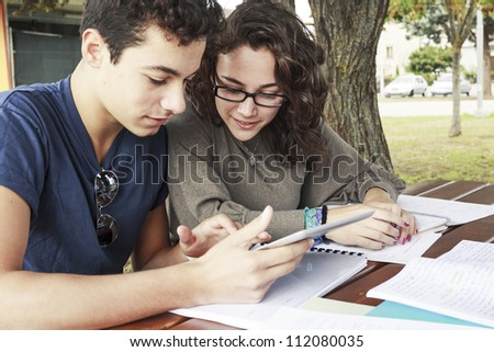 Teenagers Students around a table with a tablet