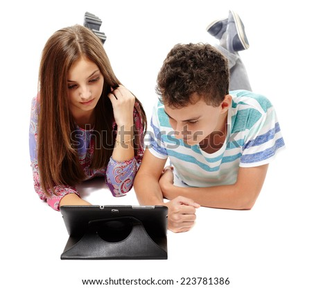 Teenagers students friends sitting on floor using a tablet, isolated on white - stock photo