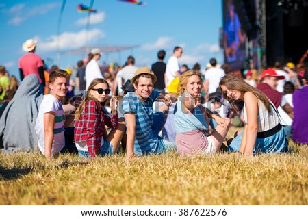 Teenagers, summer music festival, sitting in front of stage - stock photo