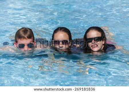 Teenagers Swimming Holidays Happy Girl Boy teenagers at beach pool summer holidays talk laughter swimming happy fun. - stock photo