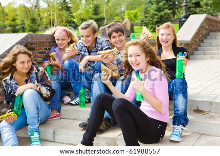 Teenagers with sandwiches and soda - stock photo