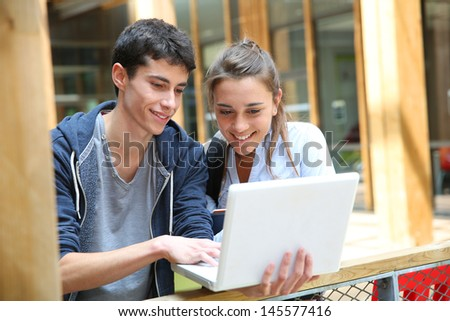 Teenagers working on laptop in school campus - stock photo