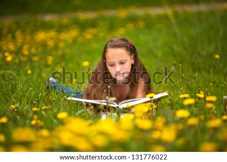 Teengirl reads a book in the meadow. - stock photo