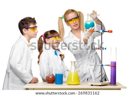 Teens and teacher of chemistry at chemistry lesson making experiments isolated on white background - stock photo