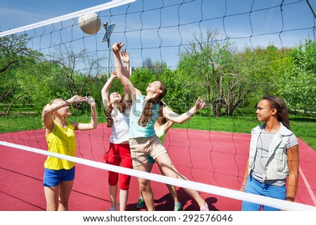 Teens are playing volleyball together on the court - stock photo
