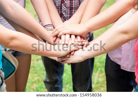 Teens' hands together. Support, teamwork, togetherness concept - stock photo