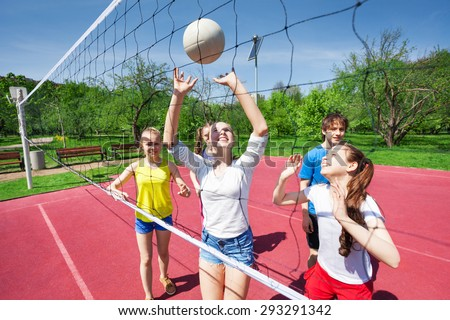Teens holding arms up and playing volleyball - stock photo