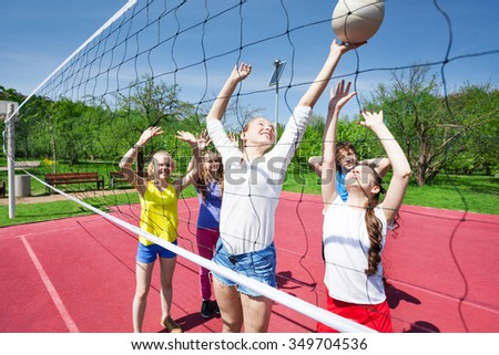 Teens in motion with arms up play volleyball near net on the playing court during sunny summer day - stock photo