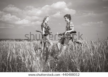 Teens on a bicycle walking in rye field - stock photo