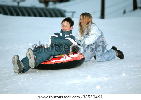 teens playing in the snow, brother and sister - stock photo