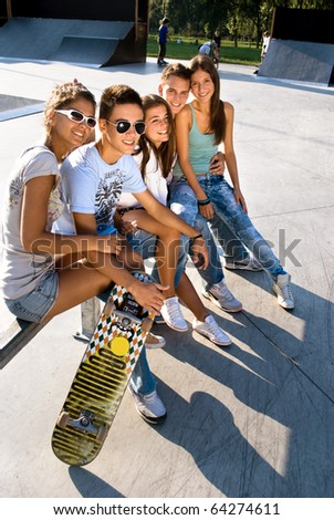 Teens relaxing in skate park - stock photo
