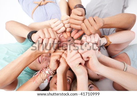 Teens relaxing on floor in a circle  with thumbs up - stock photo