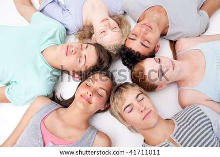 Teens sleeping on floor with heads together in a circle - stock photo