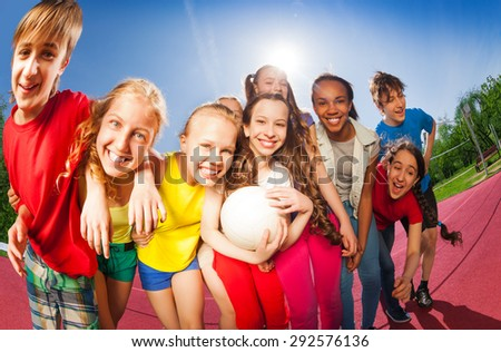 Teens standing in hug on the volleyball game court - stock photo