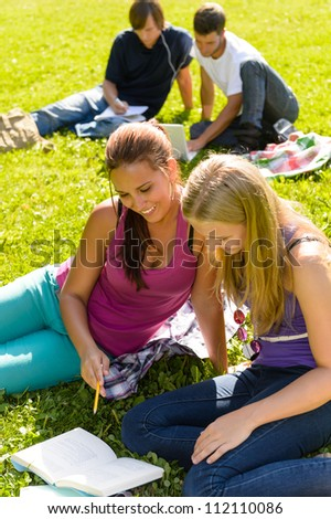 Teens studying in park reading book students happy campus research - stock photo