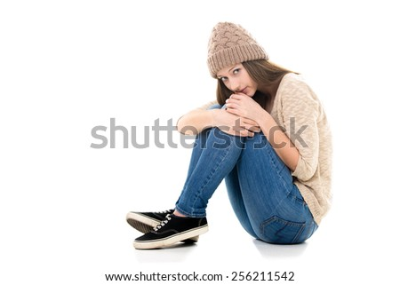 Teens troubles. Unhappy teenage girl curled-up, needs help, looking scared, copy space - stock photo