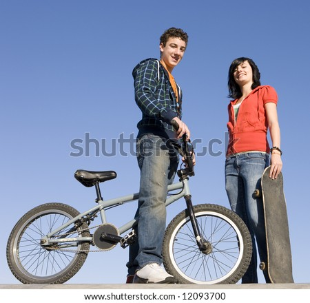 Teens with a bike and skateboard hang out at the skate park - stock photo