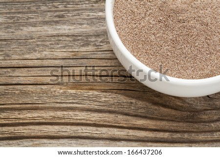 teff flour - a ceramic bowl on grained wood background - stock photo