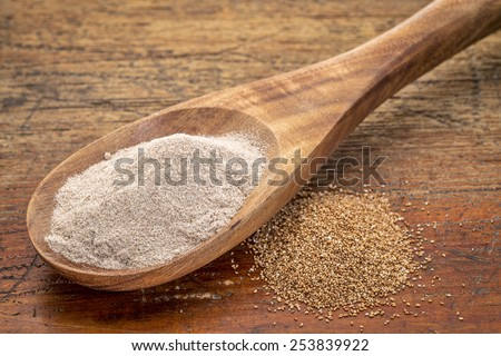 teff grain and flour i- a wooden spoon against grained wood background - stock photo