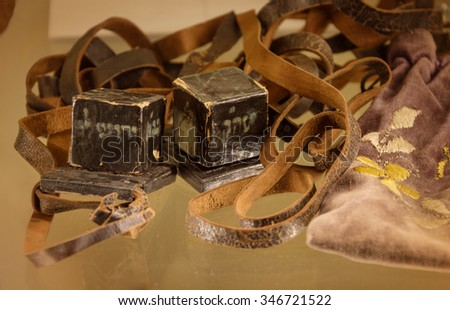 Teffilin or phylacteries. Two old small dark leather cubes with scrolls inscribed of verses from Torah, are worn by devout Jews during weekday morning God blessing. View closeup with space for text - stock photo