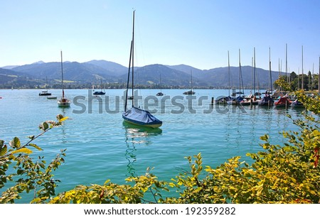 tegernsee lake shore with moored sailing boats, tranquil bavarian scenery - stock photo