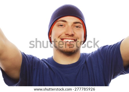 Tehnology and people concept: Happy selfie. Handsome young man holding camera and making selfie and smiling. - stock photo