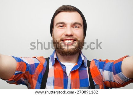 Tehnology concept: Happy selfie. Handsome young man  holding camera and making selfie and smiling. - stock photo