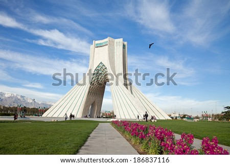 TEHRAN - APRIL 1: Azadi Square decorated with grass and flowers in springtime on April 1, 2014 in Tehran, Iran. Azadi Monument is the most famous landmark of Tehran situated in the center of Azadi sq. - stock photo