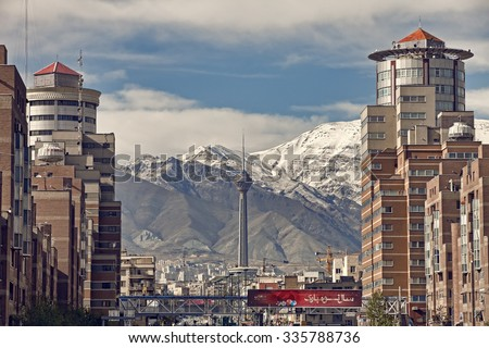 TEHRAN, IRAN - APRIL 1, 2014: Milad Tower and Navvab buildings in front of Alborz Mountains on a clear day. Milad Tower is the second most important landmark of Tehran. - stock photo