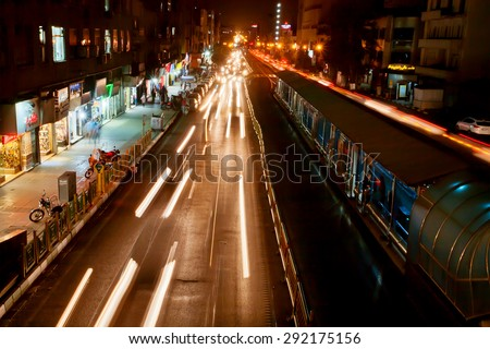 TEHRAN, IRAN - OCTOBER 6: Lights of motion blurs from speedy automobiles and metro station near at night on October 6, 2014. With a populat. of 8.3 million, Tehran is the largest city in Western Asia - stock photo
