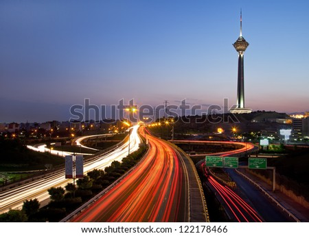 TEHRAN - JULY 16: Night shot from streets of Tehran and Illuminated Milad Tower on July 16, 2011 in Tehran, Iran. Milad Tower is the second most important landmark of Tehran, after Azadi Monument. - stock photo