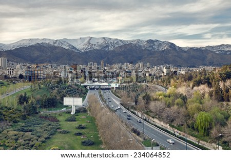Tehran skyline and greenery in front of Alborz Mountains as viewed from atop of Nature Bridge, edited with vintage filter. - stock photo