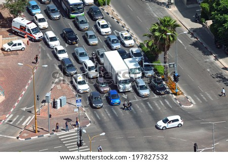 TEL-AVIV, ISRAEL - MAY 22 : Cars stop on the traffic light in rush hour. City traffic overhead view on May 22, 2014 in Tel Aviv, Israel - stock photo