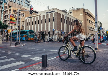Tel Aviv, Israel - October 20, 2015. Woman rides bike at Rothschild Boulevard in Tel Aviv - stock photo