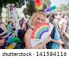 TEL AVIV - JUNE 07: Young beautiful female supporter of Pride Parade poses at the camera with rainbow fan with gay pride slogan in Hebrew in Tel Aviv, Israel on June 07, 2013 - stock photo