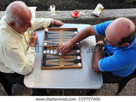 TEL AVIV - NOV 17: Old Israeli men playing backgammon on November 17 2008 in Tel Aviv, Israel.It's one of the oldest board games for two players in the world. - stock photo