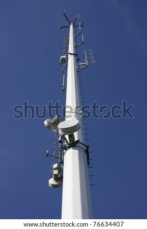 Telecommunication antenna tower station with blue sky background - stock photo
