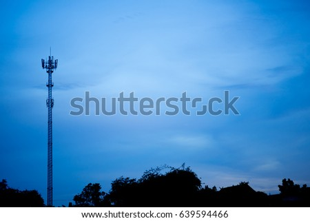 Telecommunication antenna tower with twilight blue sky on background.