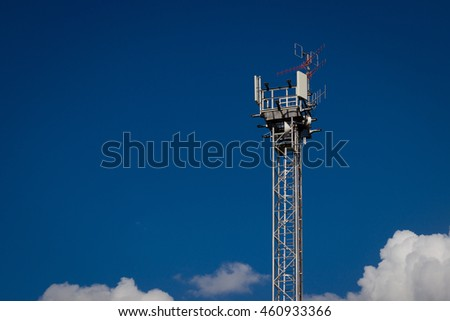Telecommunication (GSM) antenna tower (transmitter, antenna), blue sky with white clouds. - stock photo