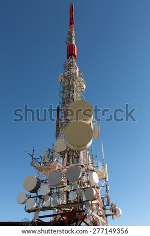 Telecommunication mast TV antennas with blue sky in sunny day - stock photo