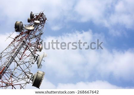 Telecommunication mast with microwave link and TV transmitter antennas on blue sky background                   - stock photo