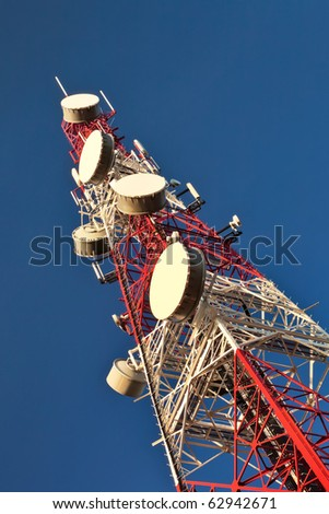 Telecommunication mast with microwave link antennas over a blue sky. - stock photo