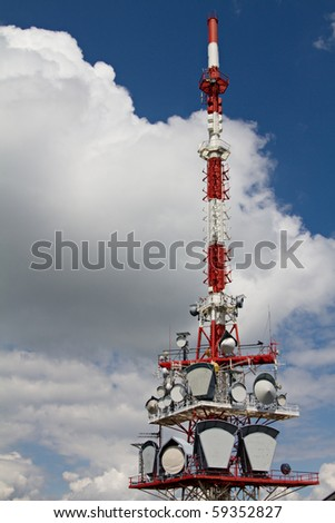 telecommunication tower against blue and cloudy sky