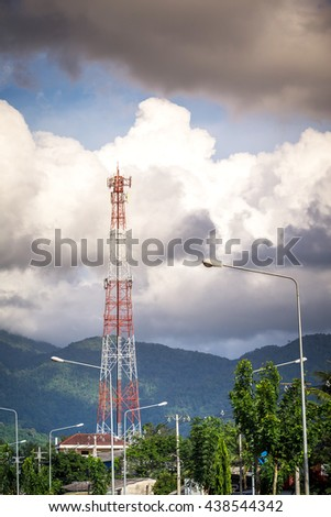 telecommunication tower in urban town with mountain in background - stock photo