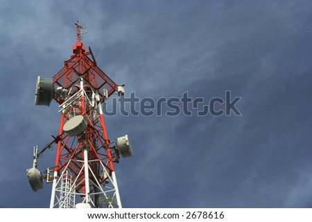 Telecommunication tower on the nice day with little clouds on blue sky