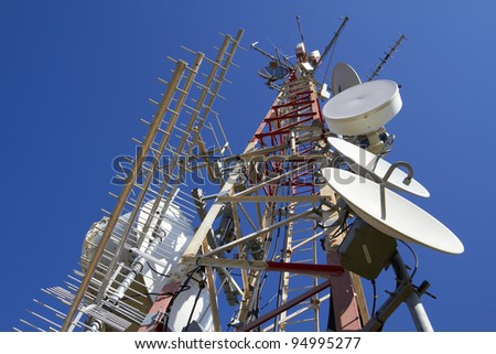 Telecommunication tower with antennas on blue sky/Telecommunication tower - stock photo