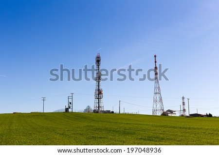 Telecommunication towers on the green field with blue sky