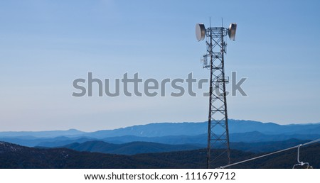 Telecommunications antennas tower in mountain - stock photo