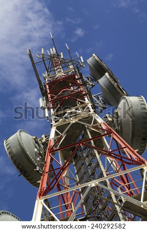 Telecommunications tower against blue sky, in red and white - stock photo