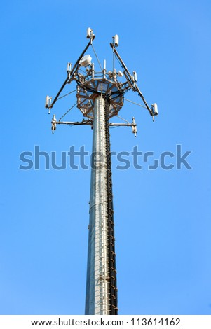 Telecommunications tower. Mobile phone base station on a blue sky background. - stock photo